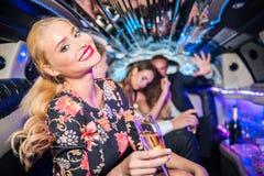 Portrait de jeune femme de sourire tenant la cannelure de champagne avec fri photographie stock libre de droits