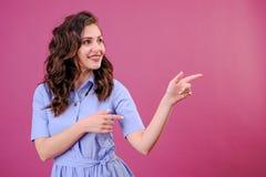 Portrait de jeune femme dirigeant le doigt de mains au coin avec le copyspace sur un fond rose images stock