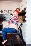 Portrait de jeune femme enceinte heureuse sur la chaise dans la cuisine Images libres de droits