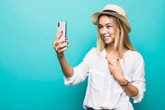 Portrait de jeune femme faisant l'appel visuel sur le smartphone, ondulant à la came d'isolement au-dessus du fond bleu photo libre de droits