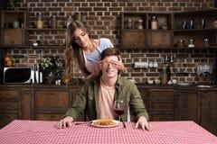 portrait de jeune femme faisant le dîner de surprise pour l'ami Photos stock