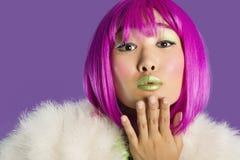 Portrait de jeune femme géniale dans le baiser de soufflement de perruque rose au-dessus du fond pourpre Photographie stock libre de droits