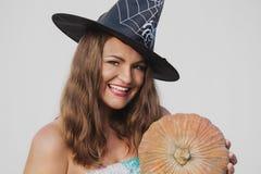 Portrait de jeune femme heureuse dans le chapeau de sorcière de Halloween avec le potiron Photographie stock libre de droits