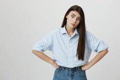 Portrait de jeune femme irritée et contrariée, tenant des mains sur la taille, regardant avec les yeux larges, blâmant quelqu'un  Images libres de droits