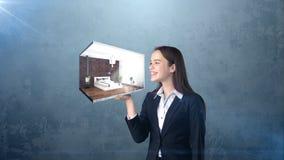 Portrait de jeune femme jugeant 3d intérieur sur la paume ouverte de main, au-dessus du fond d'isolement de studio Concept d'affa Photographie stock libre de droits