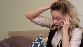 Portrait de jeune femme malheureuse faisant l'appel téléphonique contrarié à la maison clips vidéos