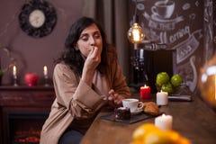 Portrait de jeune femme mignonne appr?ciant un g?teau savoureux dans un caf? au compteur de barre images stock