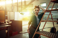 Portrait de jeune femme moderne travaillant dans l'avion à réaction se tenant prêt d'ingénierie près des escaliers regardant l'ap Image stock
