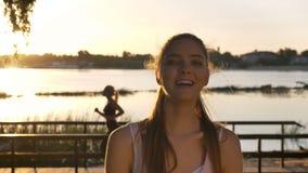 Portrait de jeune femme regardant in camera et souriant, tout autre femme courant dessus le dos, fusée de lentille, rivière et na clips vidéos