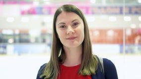 Portrait de jeune femme regardant l'appareil-photo et le sourire Patinoire sur le fond Patinage de glace de personnes banque de vidéos