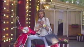 Portrait de jeune femme se reposant sur le scooter clips vidéos