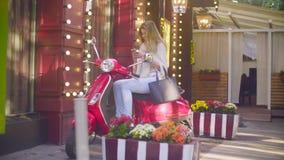 Portrait de jeune femme se reposant sur le scooter banque de vidéos