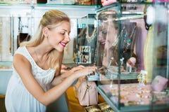 Portrait de jeune femme se tenant à côté des étalages en verre Image stock