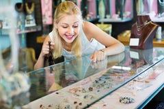Portrait de jeune femme se tenant à côté des étalages en verre Images libres de droits
