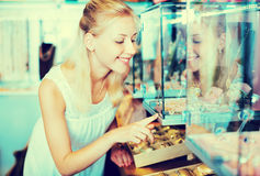 Portrait de jeune femme se tenant à côté des étalages en verre Images stock