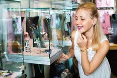 Portrait de jeune femme se tenant à côté des étalages en verre Photos stock