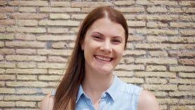 Portrait de jeune femme se tenant contre le mur de briques rouge Voyageur féminin souriant dans le mouvement lent clips vidéos