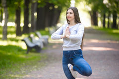 Portrait de jeune femme se tenant dans la pose d'arbre de yoga Photographie stock libre de droits