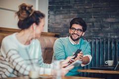 Portrait de jeune femme de sourire à une table de café regardant le téléphone intelligent Images stock