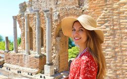 Portrait de jeune femme de sourire avec le chapeau dans le théâtre grec célèbre de Taormina, Sicile, Italie images stock