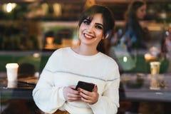 Portrait de jeune femme de sourire avec le smartphone dans des ses mains, se reposant ? la table en caf?, regardant la cam?ra La  photographie stock libre de droits
