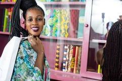 Portrait de jeune femme de sourire dans un magasin de vêtements photographie stock