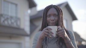 Portrait de jeune femme de sourire noire d'afro-américain sûr avec la tasse de café chaude sur la rue Mouvement lent banque de vidéos