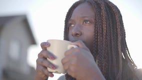 Portrait de jeune femme de sourire noire de joli afro-américain sûr avec la tasse de café chaude sur la rue lent banque de vidéos
