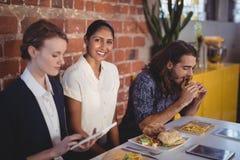 Portrait de jeune femme de sourire se reposant parmi des amis à la table avec la nourriture Image libre de droits