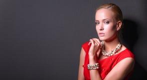 Portrait de jeune femme sur la robe rouge, fond noir d'isolement Image stock