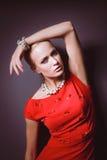 Portrait de jeune femme sur la robe rouge, fond noir d'isolement Photographie stock libre de droits