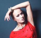 Portrait de jeune femme sur la robe rouge, fond noir d'isolement Images stock