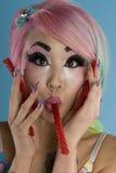 Portrait de jeune femme tenant la canne de sucrerie dans sa bouche Photo stock