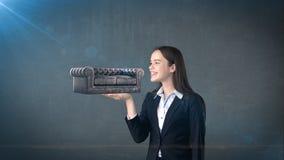 Portrait de jeune femme tenant le sofa 3D en cuir sur la paume ouverte de main, au-dessus du fond d'isolement de studio Concept d Image stock