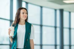 Portrait de jeune femme un embarquement de attente de salon d'aéroport Fille heureuse avec du café à entrer dans l'aéroport inter Photos stock