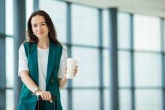 Portrait de jeune femme un embarquement de attente de salon d'aéroport Fille heureuse avec du café à entrer dans l'aéroport inter Photo stock