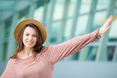 Portrait de jeune femme un embarquement de attente de salon d'aéroport Fille heureuse dans le chapeau dans l'aéroport internation Images libres de droits