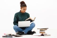 Portrait de jeune fille africaine avec l'ordinateur portable au-dessus du fond blanc photographie stock