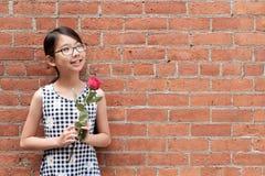 Portrait de jeune fille asiatique avec la fleur rose rouge contre le mur de briques rouge images libres de droits