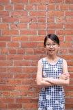 Portrait de jeune fille asiatique contre le mur de briques rouge photos libres de droits