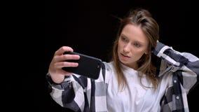 Portrait de jeune fille aux cheveux longs caucasienne dans la chemise de plaid touchant ses cheveux et faisant des selfie-photos  photographie stock