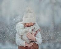 Portrait de jeune fille avec le chaton sous la neige photo libre de droits