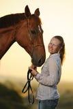 Portrait de jeune fille avec le cheval au coucher du soleil Images stock