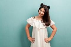 Portrait de jeune fille de belle brune heureuse avec de longs cheveux noirs dans la position blanche de robe avec des mains sur l image libre de droits