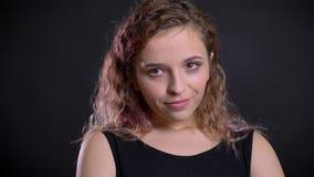 Portrait de jeune fille caucasienne avec les cheveux roses dans la confusion humble sur le fond noir clips vidéos
