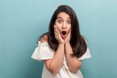 Portrait de jeune fille choquée de belle brune avec de longs cheveux droits noirs dans la position blanche de robe et de regarder photographie stock libre de droits