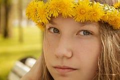 Portrait de jeune fille d'adolescent sur le banc avec la guirlande des pissenlits Images stock