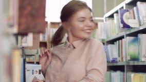 Portrait de jeune fille d'université dans la bibliothèque banque de vidéos