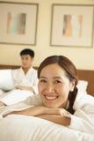 Portrait de jeune fille dans le lit avec son ami à l'arrière-plan Photographie stock