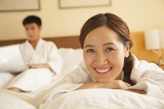 Portrait de jeune fille dans le lit avec son ami à l'arrière-plan Photos stock